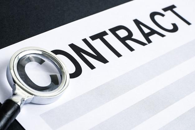 """Koncepcja przeglądu i weryfikacji projektu umowy. słowo """"umowa"""" wydrukowane na białym papierze pod lupą na czarnym tle."""