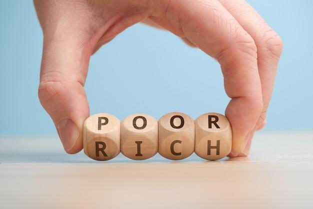 Koncepcja przejścia od statusu biednego do bogatego na drewnianych kostkach.