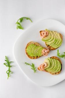 Koncepcja przekąska zdrowej diety. awokado tosty z rukolą i krewetkami na białym talerzu. strzał z góry, pionowo.
