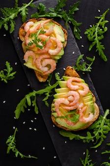Koncepcja przekąska zdrowej diety. tosty z awokado z rukolą i krewetkami. kopiuj przestrzeń, pionowa