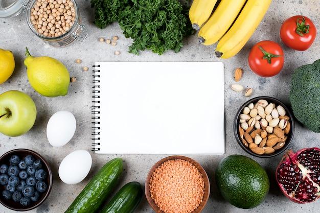 Koncepcja przepisu makieta żywności. zielone warzywa, pomidory, orzechy, owoce, soczewica, ciecierzyca, warzywa i puste puste notatnik na szarym betonowym stole. leżał płasko, widok z góry, miejsce