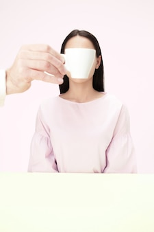Koncepcja przerwy na kawę. kobieta przed wypiciem kawy siedząc w pomieszczeniu przy stole w studio.