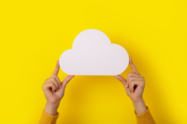 Koncepcja przetwarzania w chmurze, ręce trzymające chmurę na żółtym tle, przechowywanie w chmurze
