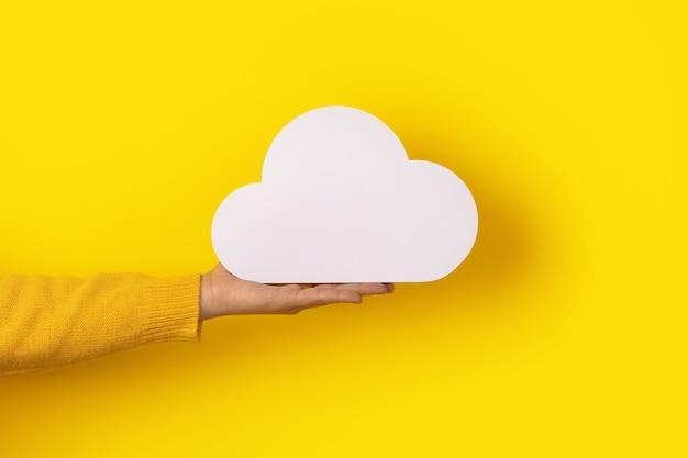 Koncepcja przetwarzania w chmurze, ręka trzymająca chmurę na żółtym tle, przechowywanie w chmurze