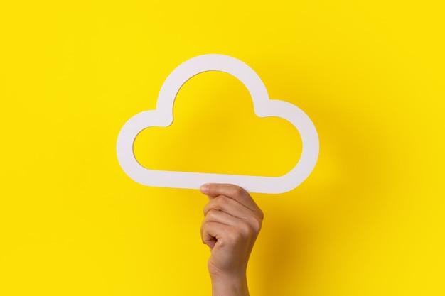 Koncepcja Przetwarzania W Chmurze, Ręka Trzymająca Chmurę Na żółtym Tle, Przechowywanie W Chmurze Premium Zdjęcia