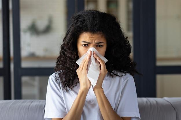 Koncepcja przeziębienia i grypy. młoda afroamerykanka z przeziębieniem, kichaniem i używaniem serwetki