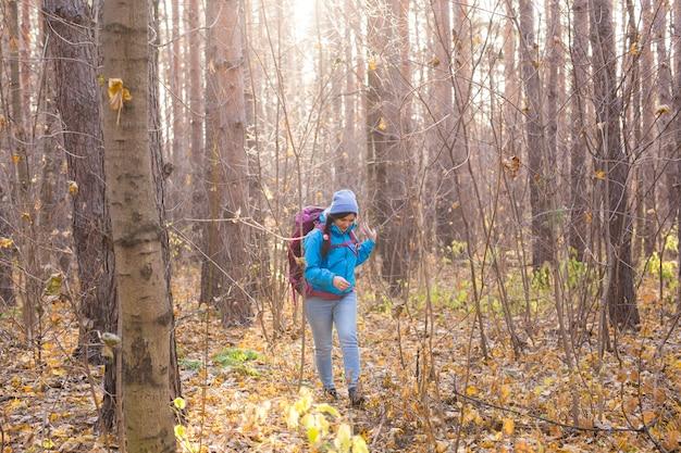 Koncepcja przygody, podróży, turystyki, wędrówek i ludzi - uśmiechnięta kobieta spacerująca z plecakami na jesiennym naturalnym tle.