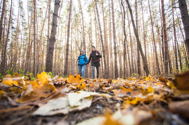 Koncepcja przygody, podróży, turystyki, wędrówek i ludzi - uśmiechnięta para spacerująca z plecakami na jesiennym naturalnym tle.