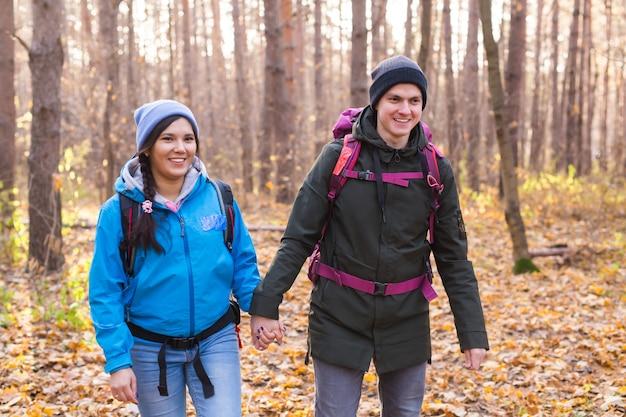 Koncepcja przygody, podróży, turystyki, wędrówek i ludzi - uśmiechnięta para spacerująca z plecakami po jesiennym lesie naturalnym