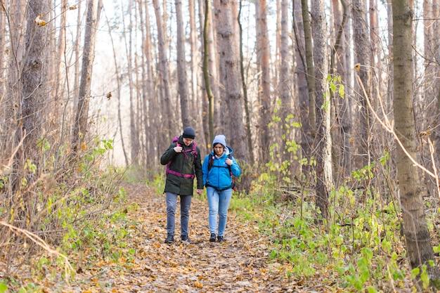 Koncepcja przygody, podróży, turystyki, wędrówki i ludzi - uśmiechnięta para spacerująca z plecakami
