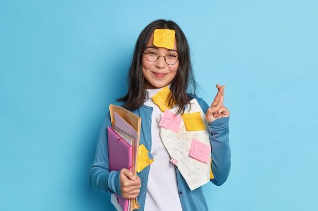 Koncepcja przygotowania do egzaminu. zadowolona azjatka trzyma kciuki i wierzy w szczęście, a badania finansowe przygotowują do spotkania.
