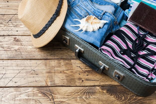 Koncepcja przygotowania podróży z walizką, ubrania i akcesoria na starym drewnianym stole. widok z góry kopiowanie miejsca