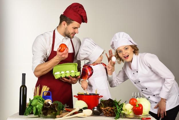 Koncepcja przyjaznej rodziny, wzajemnej pomocy, wsparcia, gotowania - szczęśliwa rodzina w kuchni. zdrowa żywność w domu. urocze dziecko w kapeluszu szefa kuchni z rodzicami. matka i ojciec uczy chłopca, jak gotować.
