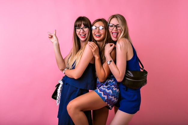 Koncepcja przyjaźni w pozytywnych relacjach, trzy wesołe ładne kobiety bawiące się razem, przytulanie i zaskakujące emocje, dopasowane kolorystycznie wieczorowe stroje i dodatki, urocze emotikony, zabawa w grupie.