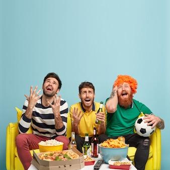 Koncepcja przyjaźni, wypoczynku, sportu, rozrywki. przygnębieni, pełni nadziei trzej młodzi faceci skupieni w górę z nieszczęśliwymi minami, proszą o szczęście drużynie piłkarskiej, którą kibicują, wierzą w sukces
