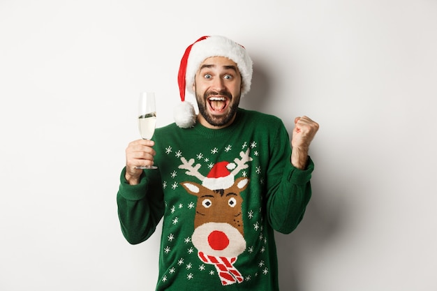 Koncepcja przyjęcia i święta bożego narodzenia. podekscytowany mężczyzna w santa hat świętujący nowy rok, pijący szampana i radujący się, stojący na białym tle