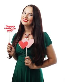 Koncepcja przyjęcia: młoda piękna kobieta ubrana w zieloną sukienkę, trzymając papierowe serca