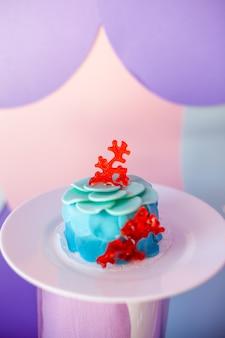 Koncepcja przyjęcia urodzinowego. stolik dla dzieci z babeczkami z niebieskim i czerwonym blatem i dekorowanymi przedmiotami w jasnych kolorach niebieskim i fioletowym. sezon letni pyszny na imprezie.
