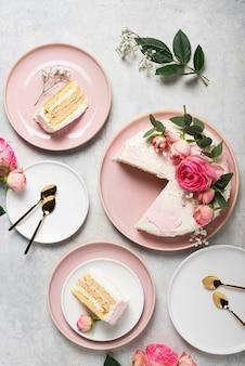 Koncepcja przyjęcia urodzinowego z różowym białym ciastem ozdobionym różowymi różami, widok z góry na dół
