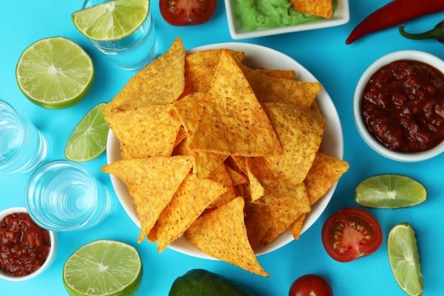 Koncepcja przyjęcia z tequilą, guacamole i frytkami na niebieskim tle