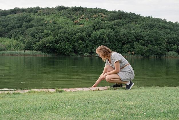 Koncepcja przyrody i podróży. kobieta siedząca nad jeziorem