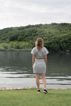 Koncepcja przyrody i podróży. widok kobiety stojącej w pobliżu jeziora z tyłu