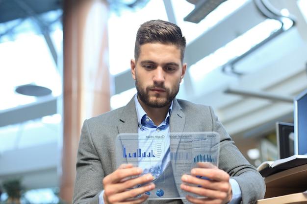 Koncepcja przyszłości. biznesmen analizujący statystyki finansowe wyświetlane na futurystycznym przezroczystym ekranie tabletu