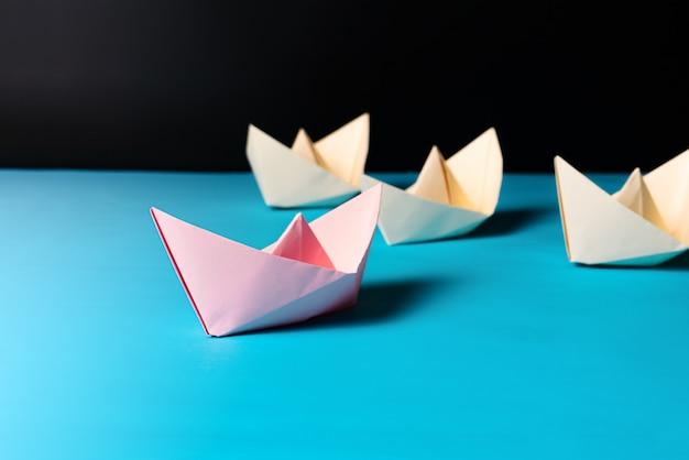 Koncepcja przywództwa, statek z różowego papieru prowadzi żółty członek zespołu statku