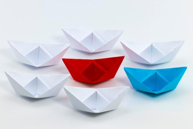 Koncepcja przywództwa z czerwonym papierowym statkiem prowadzącym wśród białych.