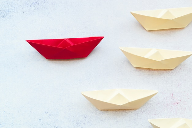 Koncepcja przywództwa za pomocą czerwonego papieru statku wśród białych na tle
