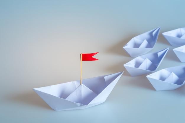 Koncepcja przywództwa za pomocą statku papieru z czerwoną flagą na niebieskim tle