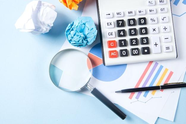 Koncepcja pulpitu. statystyka, kalkulator pognieciony papier i lupa na stole