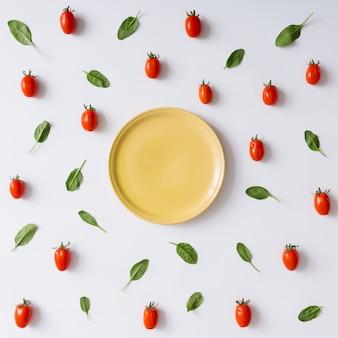 Koncepcja pusty talerz z pomidorkami cherry i wzór liści bazylii. leżał na płasko.
