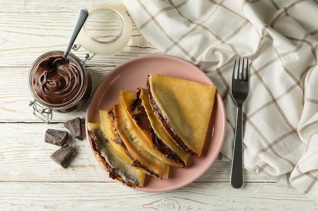 Koncepcja pyszne śniadanie z naleśnikami z pastą czekoladową na białym tle drewnianych