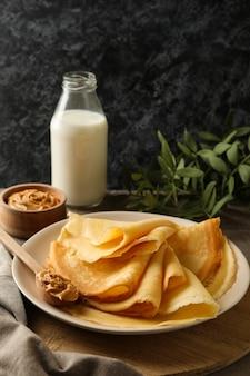 Koncepcja pyszne śniadanie z talerzem naleśników z masłem orzechowym na desce
