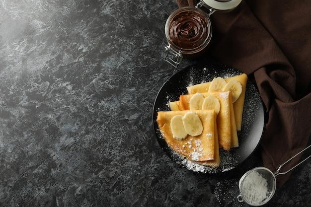 Koncepcja pysznego śniadania z naleśnikami z cukrem pudrem i bananem na czarnej smokey powierzchni
