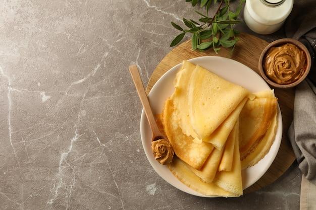 Koncepcja pysznego śniadania z naleśnikami z masłem orzechowym i mlekiem na szarym stole