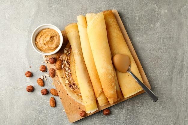 Koncepcja pysznego śniadania z naleśnikami z masłem orzechowym i orzechami na szarym stole
