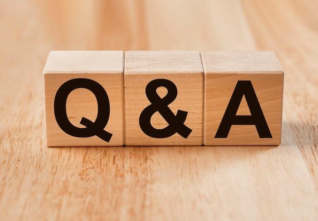 Koncepcja qa lub q w pytaniach ekologicznych. akronim qna na drewnianych kostkach na drewnie.