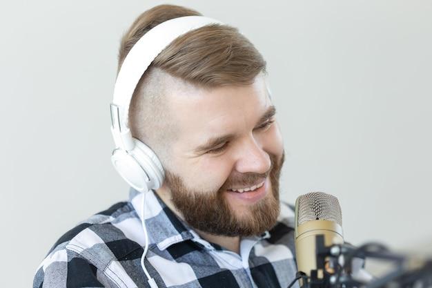 Koncepcja radia i dj - uśmiecha się człowiek z mikrofonem i dużymi słuchawkami