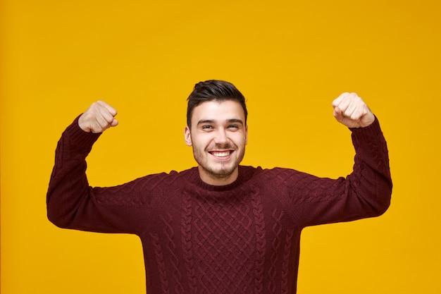 Koncepcja radości, szczęścia, wygranej i sukcesu. szczęśliwy, charyzmatyczny młody mężczyzna rasy kaukaskiej w stylowym swetrze zaciskający pięści, wyrażający szczerą reakcję na dobre wieści, mający podekscytowany wygląd