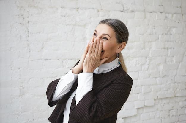 Koncepcja radości, zabawy, pozytywnych ludzkich emocji i uczuć. portret szczęśliwa wesoła dojrzała kobieta ubrana w białą koszulę i kurtkę zakrywającą usta, śmiejąc się z żartu lub ciesząc się z dobrych wiadomości