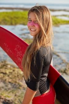 Koncepcja raju surfingowego. dość młoda surferka z długimi prostymi włosami, nosi deskę surfingową, na twarzy ma odporny na słońce krem cynkowy
