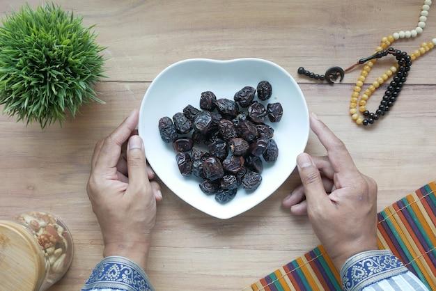 Koncepcja ramadanu ręki trzymającej miskę owoców daty