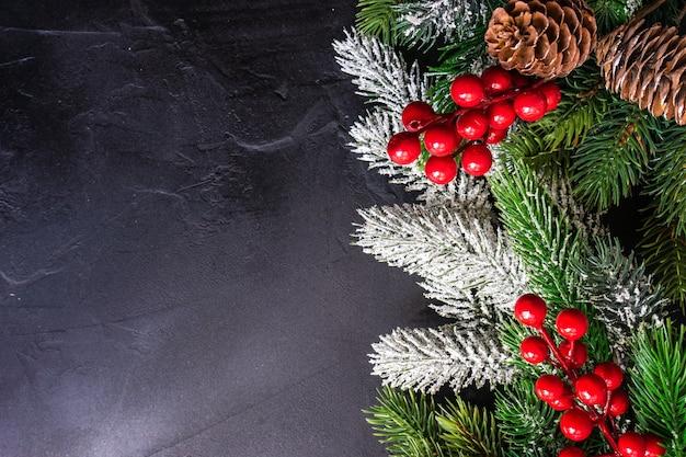 Koncepcja ramy bożonarodzeniowej z gałęziami choinki i czerwonym wystrojem wakacyjnym na szarej kamiennej powierzchni z miejscem na kopię