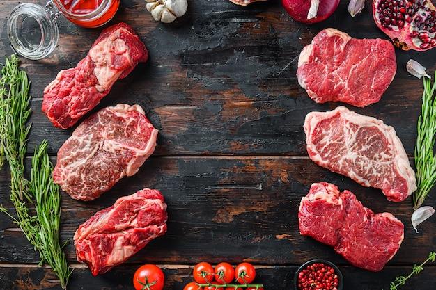 Koncepcja ramy steki mięsne wołowe, z różnymi kawałkami steków na ciemnym starym drewnianym stole
