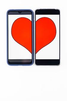 Koncepcja randek online. połówki serca na dwóch ekranach smartfonów. koncepcja walentynki