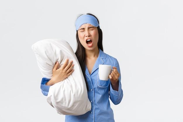 Koncepcja rano styl życia, śniadanie i ludzie. dziewczyna z bezsennością w masce do spania i piżamie, przytulająca poduszkę, pijąca kawę i ziewająca, próbująca przebudzenia, białe tło