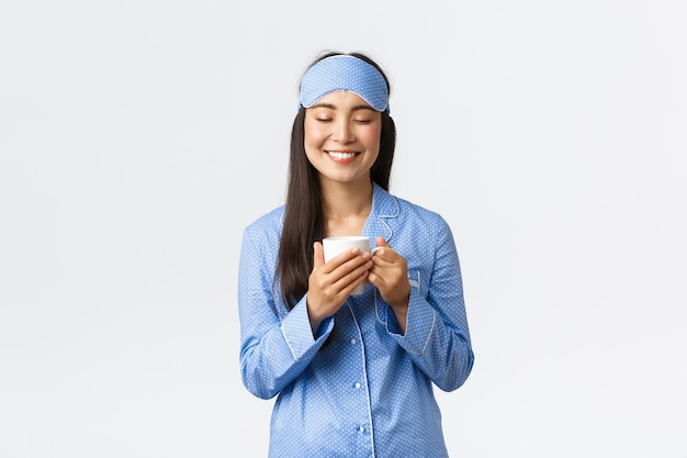 Koncepcja rano styl życia, śniadanie i ludzie. marzycielski szczęśliwy uśmiechający się azjatycki dziewczyna w niebieskiej piżamie i masce do spania zamyka oczy marząc na jawie z filiżanką kawy, pobudka, białe tło.