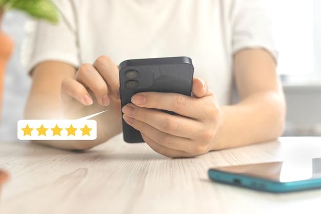 Koncepcja recenzji klientów z ikoną oceny lub opinii, złota pięciogwiazdkowa recenzja usługi, kobieta ze smartfonem